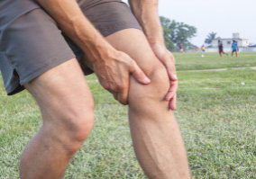 30122550 - closeup of athletic caucasian man holding his painful knee on soccer field